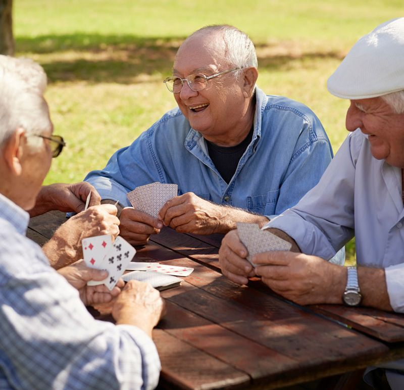 Male residents playing cards outside