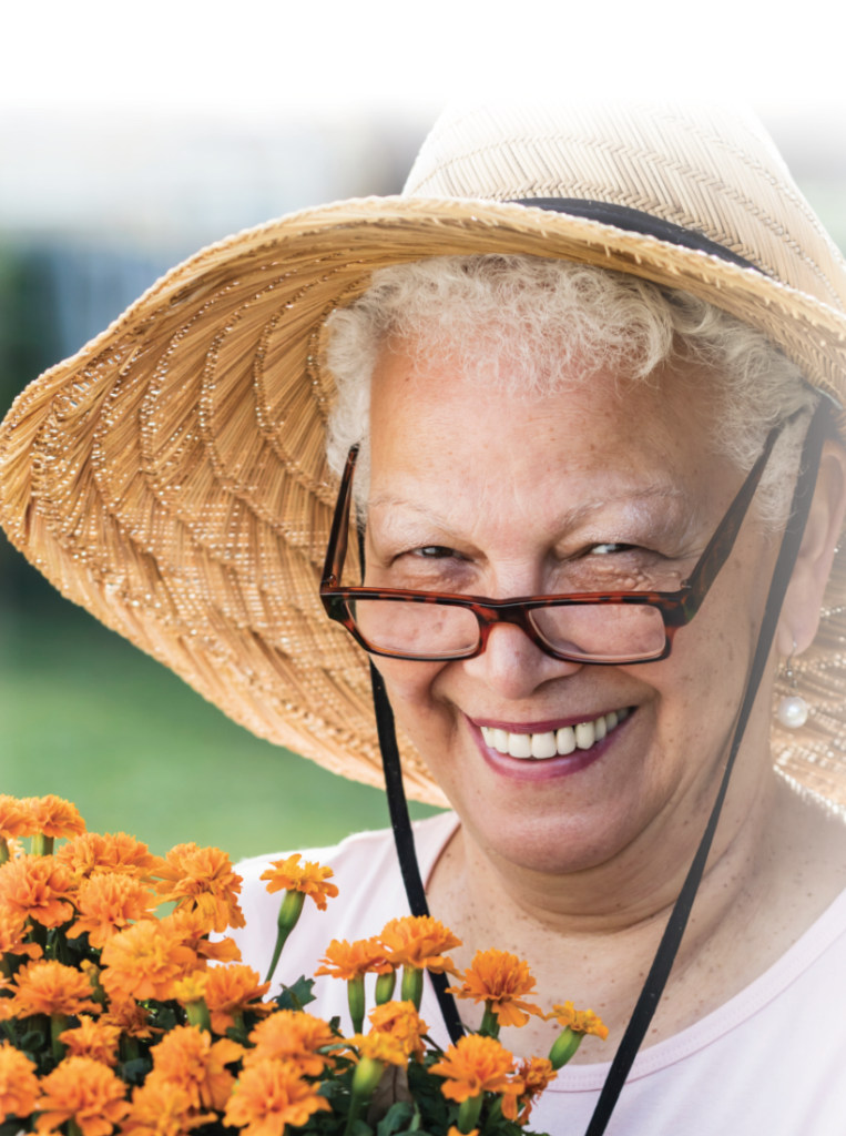 Senior woman with glasses and hat holding marigold plans
