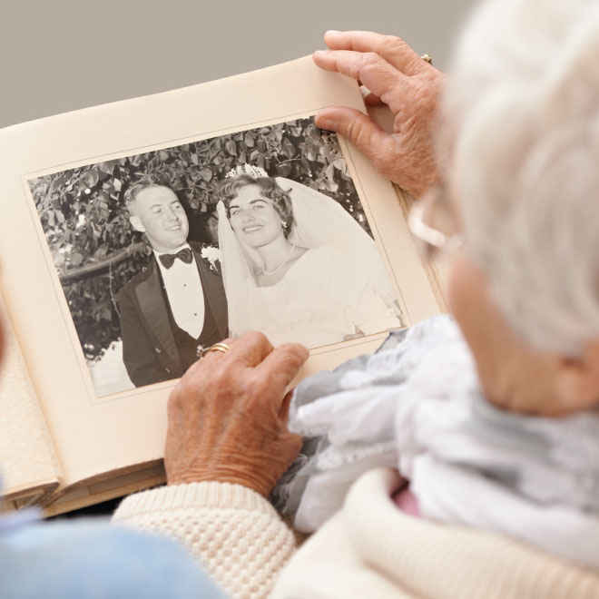 Senior woman and man looking at an old photo album
