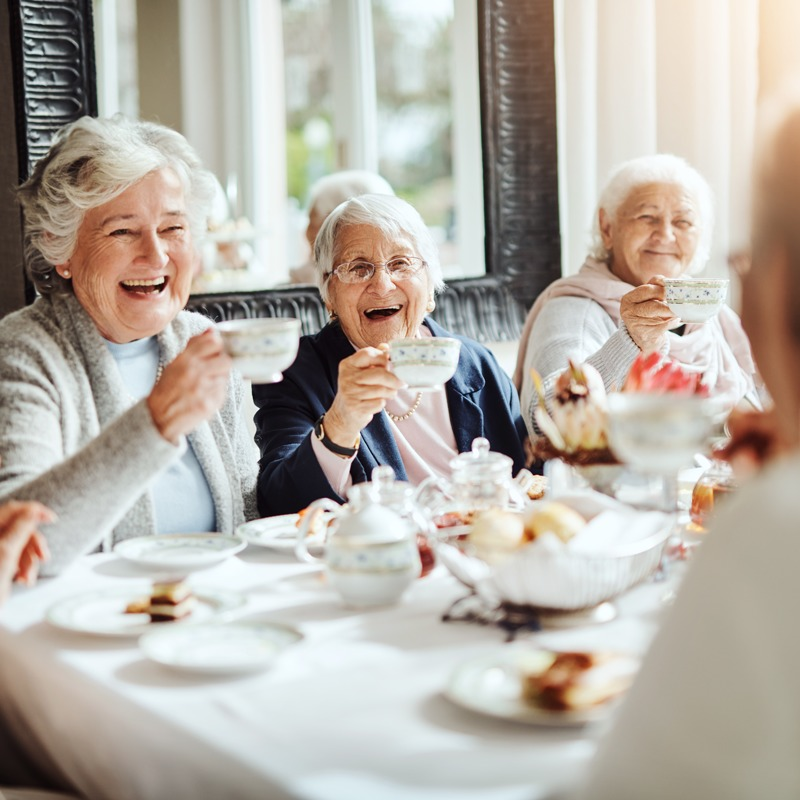 Group of senior women having tea and dessert together