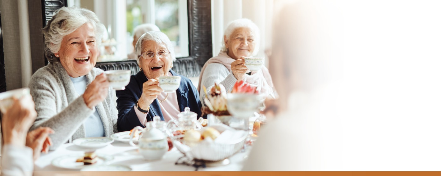 Three senior women lifting their tea cups in a toast and laughing.