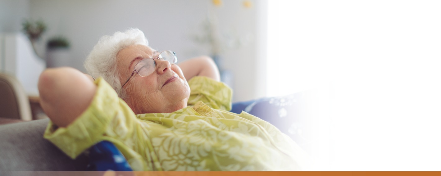 Senior woman reclining with eyes closed and a smile on her face.